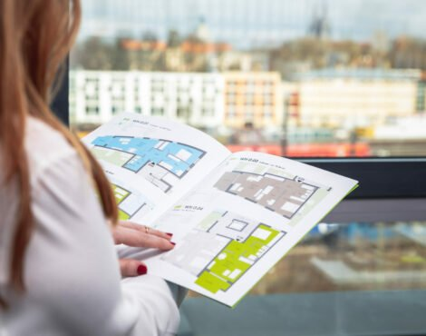 eine Dame schaut ein Heft mit Grundrissen an